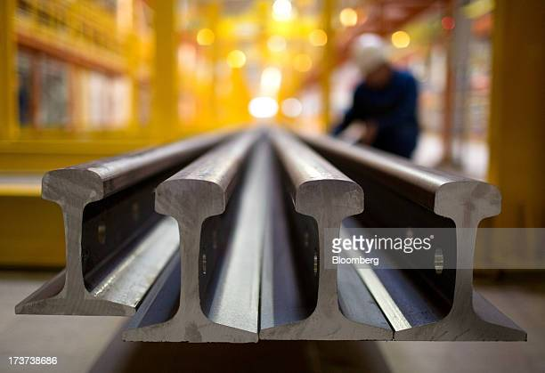 Long lengths of steel train rails sit on the production line during manufacture in the universal rail and beam rolling mill at OAO Mechel's...
