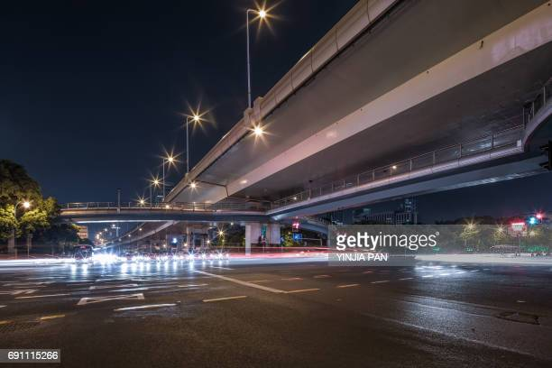 Long light trails of the crossroads under the elevated road