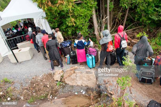 A long line of asylum seekers wait to illegally cross the Canada/US border near Champlain New York on August 6 2017 In recent days the number of...