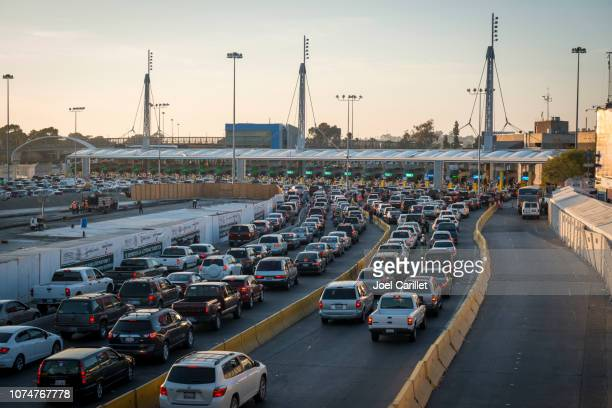 long line of cars crossing mexican border at tijuana/san ysidro - national border stock pictures, royalty-free photos & images