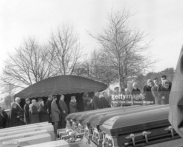 Long line of mourners some weeping file past row of six caskets at St Charles Cemetery in Amityville LI for Ronald DeFeo his wife Louise and their...