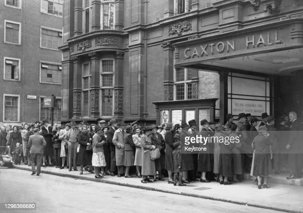 Long line of people queuing for their new ration card books along the street outside Caxton Hall National Registration Office on 10th January 1940 in...
