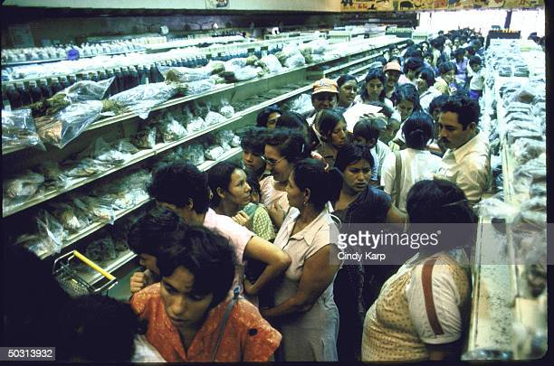 A long line of people waiting at a supermarket for a chance to buy some of the meager meat supply available