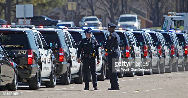 A long line of police vehicles line the entrance to Pennington Field in Fort Worth Texas at a memorial service for Euless Texas police officer David...