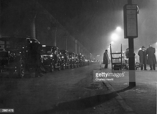 A long line of taxis waiting for customers on a winter night at Paddington Station London Original Publication Picture Post 4960 Round The Clock With...