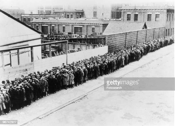 A long line of unemployed and homeless men wait outside to get free dinner at the municipal lodging house during the Great Depression in New York USA...