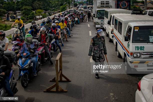 Long lines of motorists form at a quarantine checkpoint on the first day of a reimposed lockdown to curb the spread of COVID-19, on August 4, 2020 in...