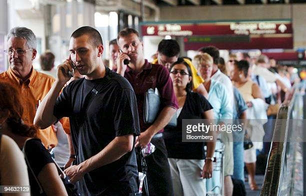 Long lines of passengers queue up to go through increased security check points as news rules for carry on luggage cause long delays at the...