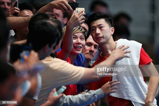 Long Ma of China poses for a photo with fans after defeating Aruna Quadri of Nigeria during the Men's Singles Quarterfinal 2 Table Tennis on Day 4 of...