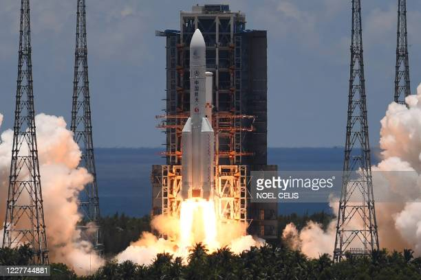 Long March-5 rocket, carrying an orbiter, lander and rover as part of the Tianwen-1 mission to Mars, lifts off from the Wenchang Space Launch Centre...