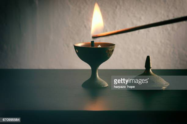 long match lighting an incense cone. - incense stock photos and pictures