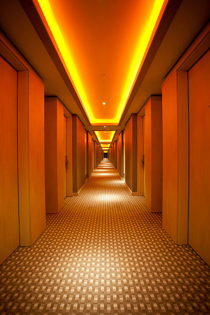 Long, narrow corridor with retro themed carpet and lighting