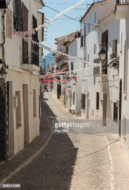 long narrow street in a whitewashed street in altea, spain - whitewashed stock photos and pictures