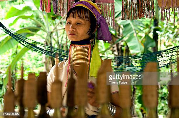 A long neck woman sits behind small wooden carvings of long necks at her souvenir stall in Nai Soi village Northern Thailand The long necks are...