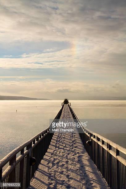 long pier on lake on winter morning - スカネアトレス湖 ストックフォトと画像