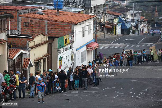 A long que of people queue up before sunrise to buy basic foodstuffs at a supermarket on March 8 2014 in San Cristobal the capital of Tachira state...