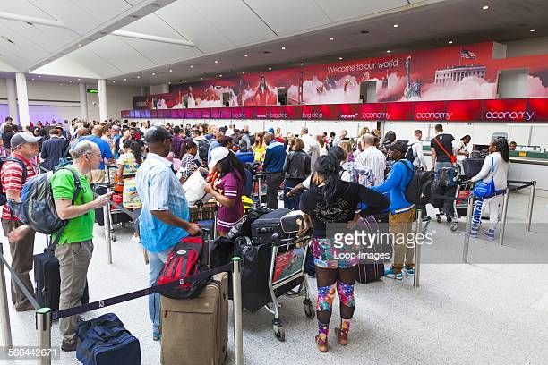 Long queue of passengers waiting to check in at Virgin Atlantic desks