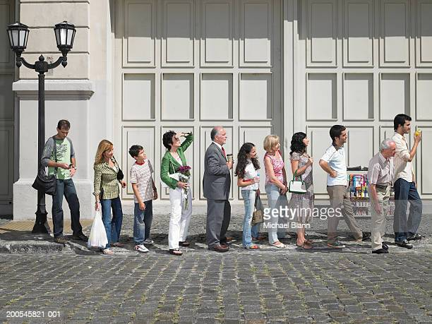 long queue of people in street, side view - wachten stockfoto's en -beelden