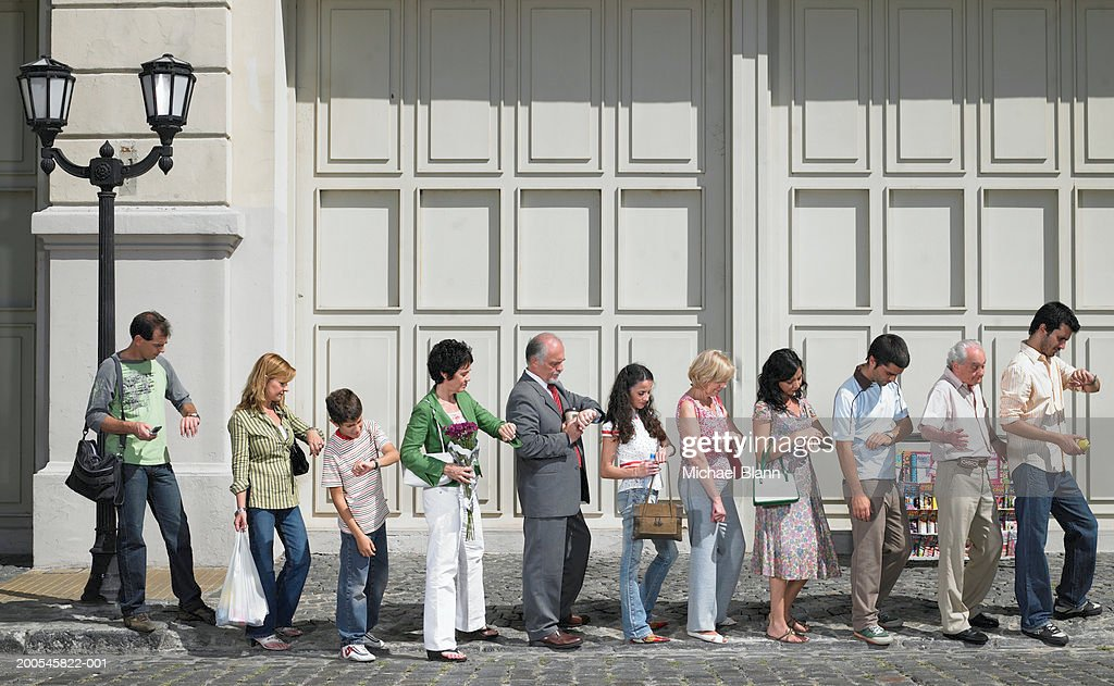 Long queue of people in street, side view : Stock Photo