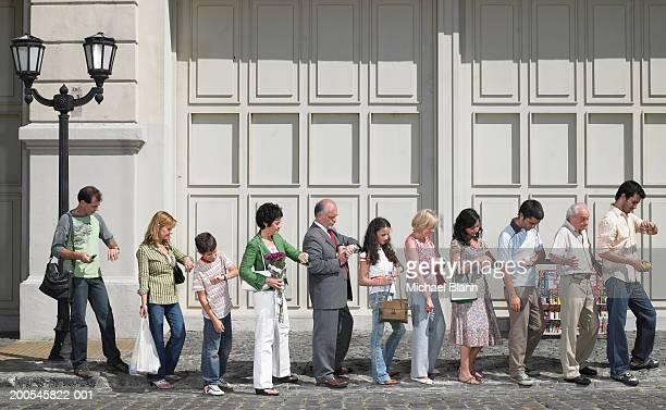 long queue of people in street, side view - ongeduldig stockfoto's en -beelden