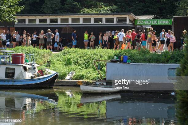 A long queue of people waits to gain entrance to the Jesus Green Lido near to the River Cam on July 25 2019 in Cambridge United Kingdom The Met...