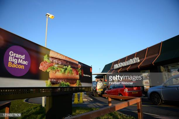 Long queues outside a McDonald's restaurant and drive thru prior to closure on March 23 2020 in Weymouth United Kingdom Coronavirus pandemic has...