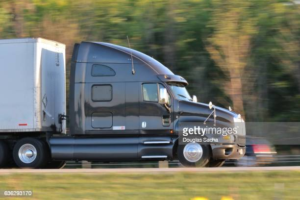 long range semi tractor with sleeper cabin and overhead air dam on the highway - international brotherhood of teamsters stock photos and pictures