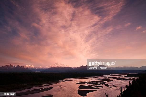 a long range view of denali (mt. mckinley) overlooking the susitna river on a cloudy day at sunset. - mt. susitna stock pictures, royalty-free photos & images