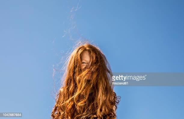 long red hair covering face of a girl under blue sky - só uma menina - fotografias e filmes do acervo