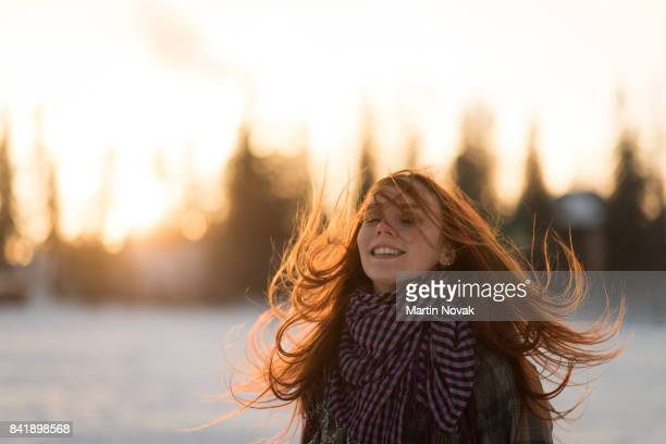 Long red hair woman flipping hair in the air