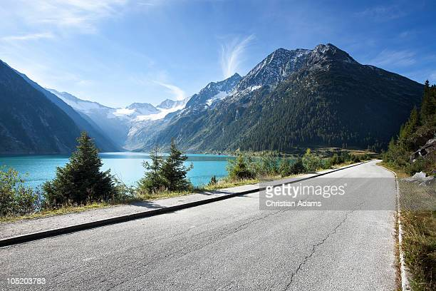 long road along mountain lake - nature stock pictures, royalty-free photos & images
