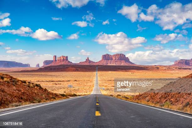 long road at monument valley utah side usa - utah stock pictures, royalty-free photos & images
