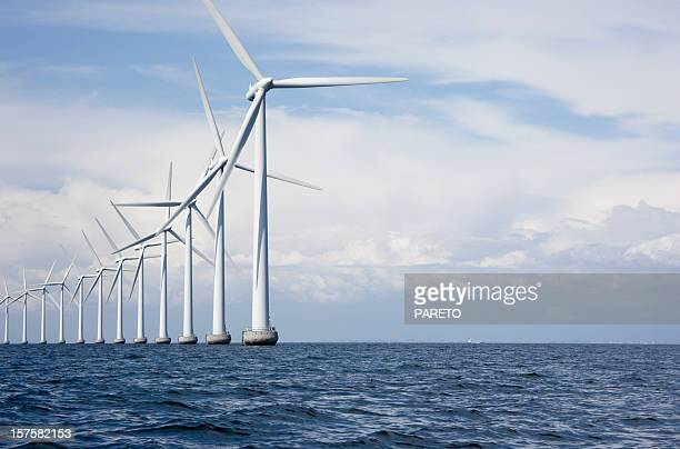 long row a very tall windmills offshore - windmills stock photos and pictures