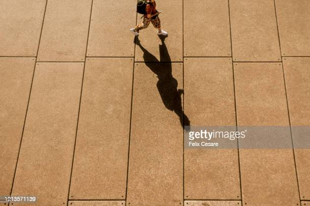 a long shadow of a person walking - coronavirus australia stock pictures, royalty-free photos & images