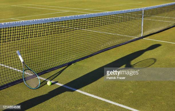 long shadow of person with tennis racket still life on grass lawn tennis court - tennis racquet stock pictures, royalty-free photos & images