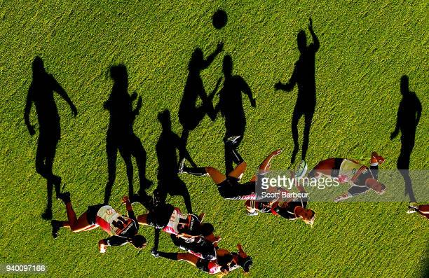 Long shadows are cast by players as Jocelyn Davis of the Rebels competes for the ball during the round four Super W match between the Rebels and the...