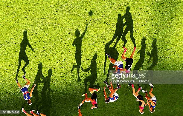 Long shadows are cast by players as Mitch Wallis of the Bulldogs passes the ball during the 2016 AFL Round 08 match between the Melbourne Demons and...