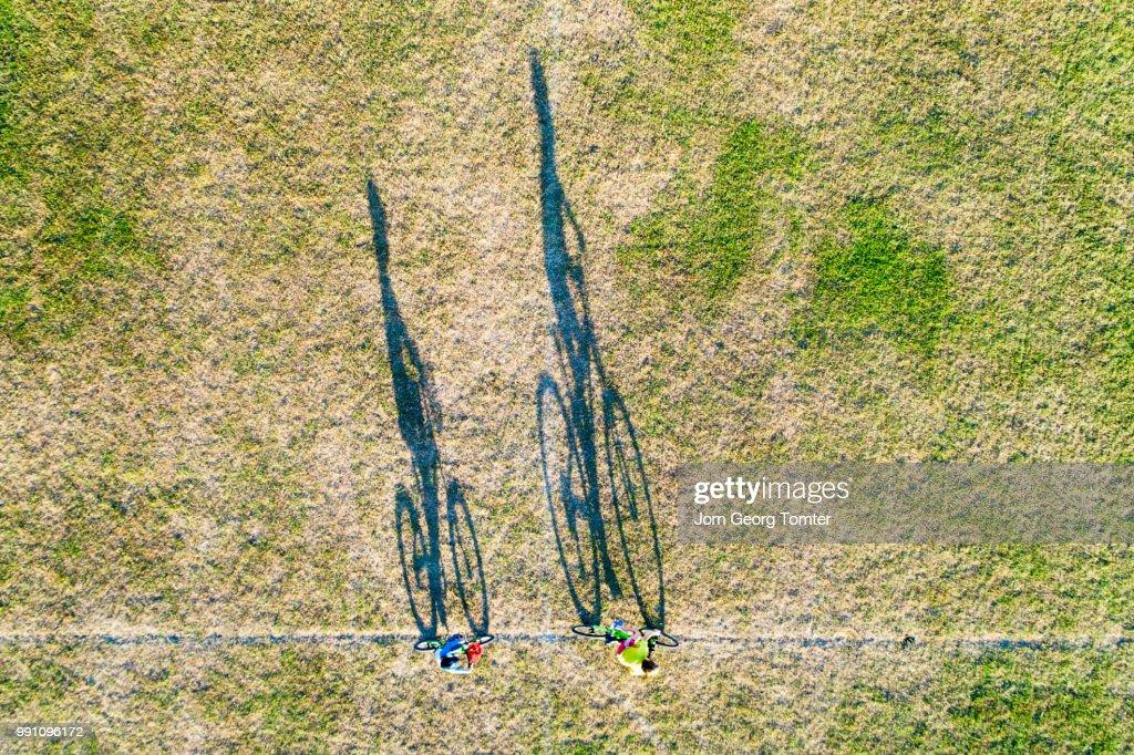 Long shadows of two boys cycling : Foto de stock