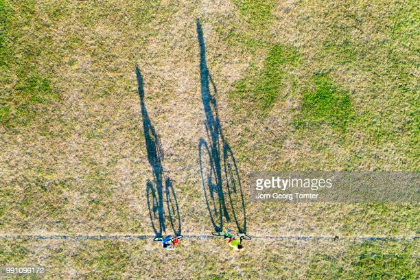 long shadows of two boys cycling - image stock pictures, royalty-free photos & images