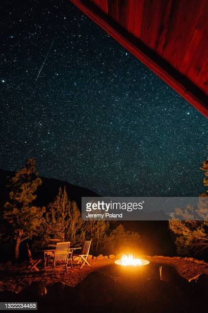 long shooting star seen from a modern a-frame tiny home at night with millions of bright stars and a gas fire pit on a clear night in the summer - national forest stock pictures, royalty-free photos & images