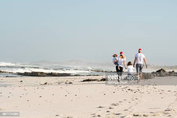 long shot as family walk down the beach early christmas morning - wide shot stock pictures, royalty-free photos & images