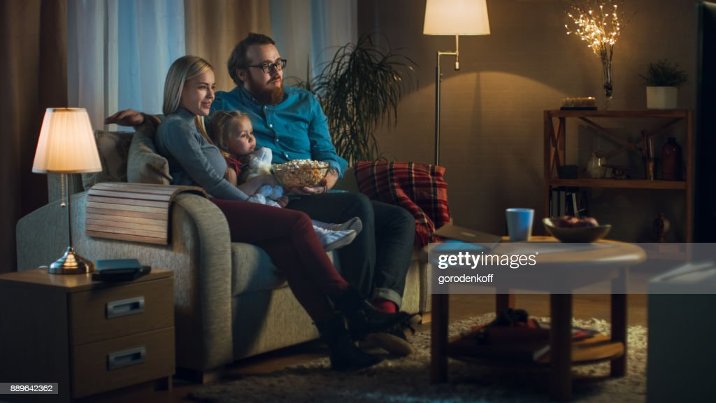 Long Shot of a Father, Mother and Little Girl Watching TV. They Sit on a Sofa in Their Cozy Living Room and Eat Popcorn. It's Evening. : Stock Photo