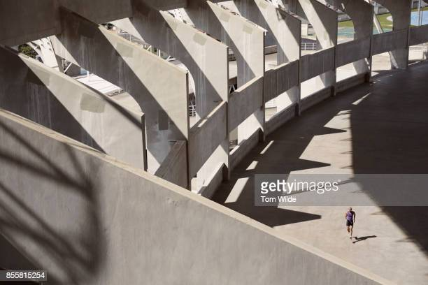 long shot of a male athlete as he runs through a concrete stadium - center athlete stock pictures, royalty-free photos & images