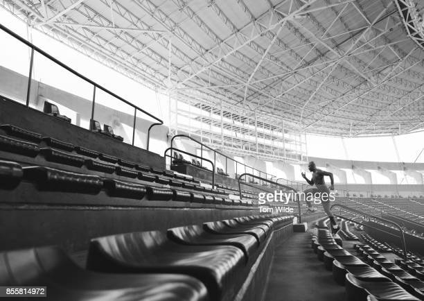 Long shot of a male athlete running up the stadium chairs
