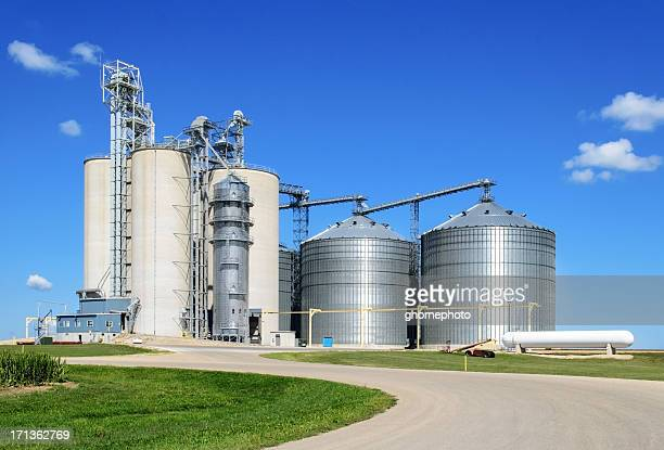 long shot of grain elevator facility on a sunny day - silo stock photos and pictures