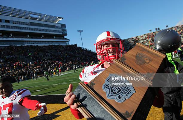 Long snapper PJ Mangieri of the Nebraska Cornhuskers carries the Heroes Game trophy after the game against the Iowa Hawkeyes on November 23 2012 at...