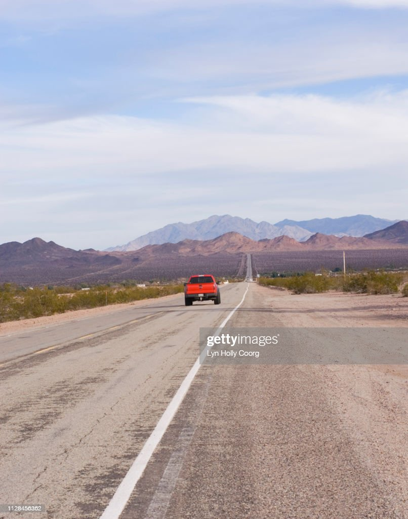 Long straight highway in Mojave Desert California USA with red truck : Stock Photo