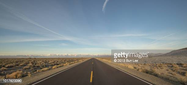 a long straight road into the snow-topped mountain - horizon stockfoto's en -beelden