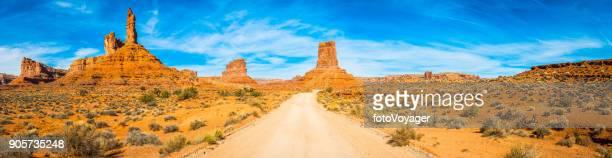 Long straight road through desert Monument Valley mesas panorama Utah