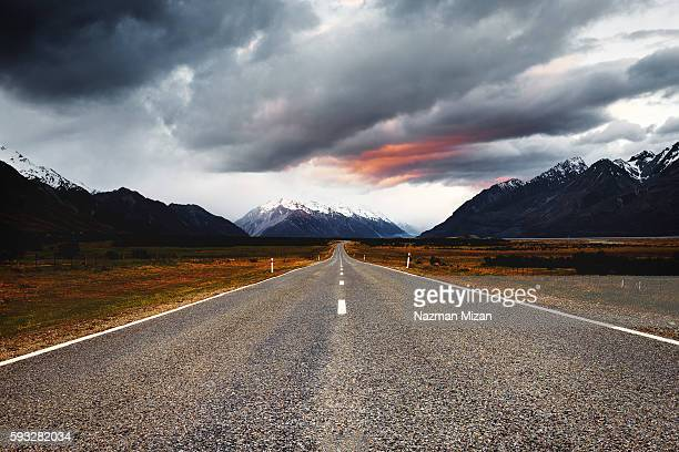 A long straight road toward Mt Cook National park during sunset.